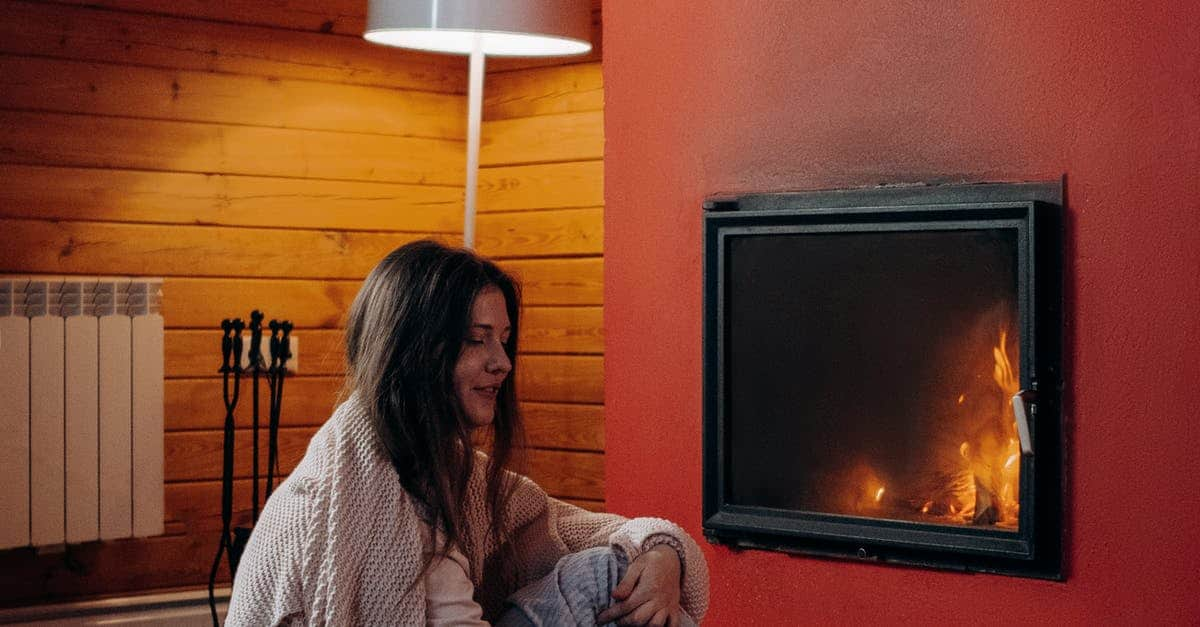 A person standing in front of a fireplace