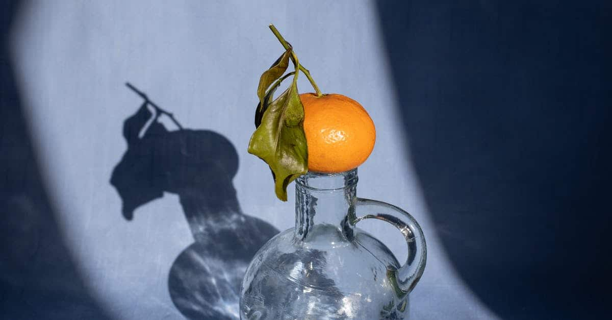 A glass of orange juice next to a vase on a table